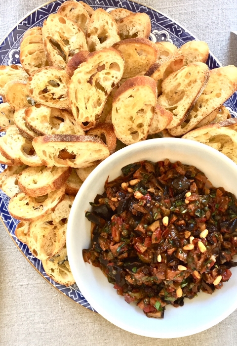 Eggplant Caponata epitomizes summer. The eggplant sops up the olive oil so use a good one. The dish is layered and made rich with salty and sweet notes. It's perfect served at room temperature as an appetizer but also delicious on burgers, over grilled meats and chicken, or layered in a sandwhich. Makes about 3-4 cups