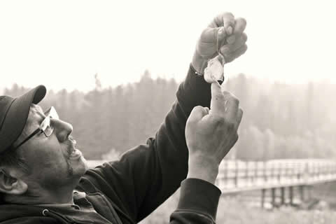 "Chief Billy Joe Laboucan shows how to make a ""grouse balloon."" It is the inflated stomach of a grouse, which in this case contained three red berries. An old Lubicon Cree tradition was to tie and hang one of these in a lodge somewhere, and when a person was caught standing under it, they had to tell a story. Photo credit:  www.invisiblehistory.blogspot.com"