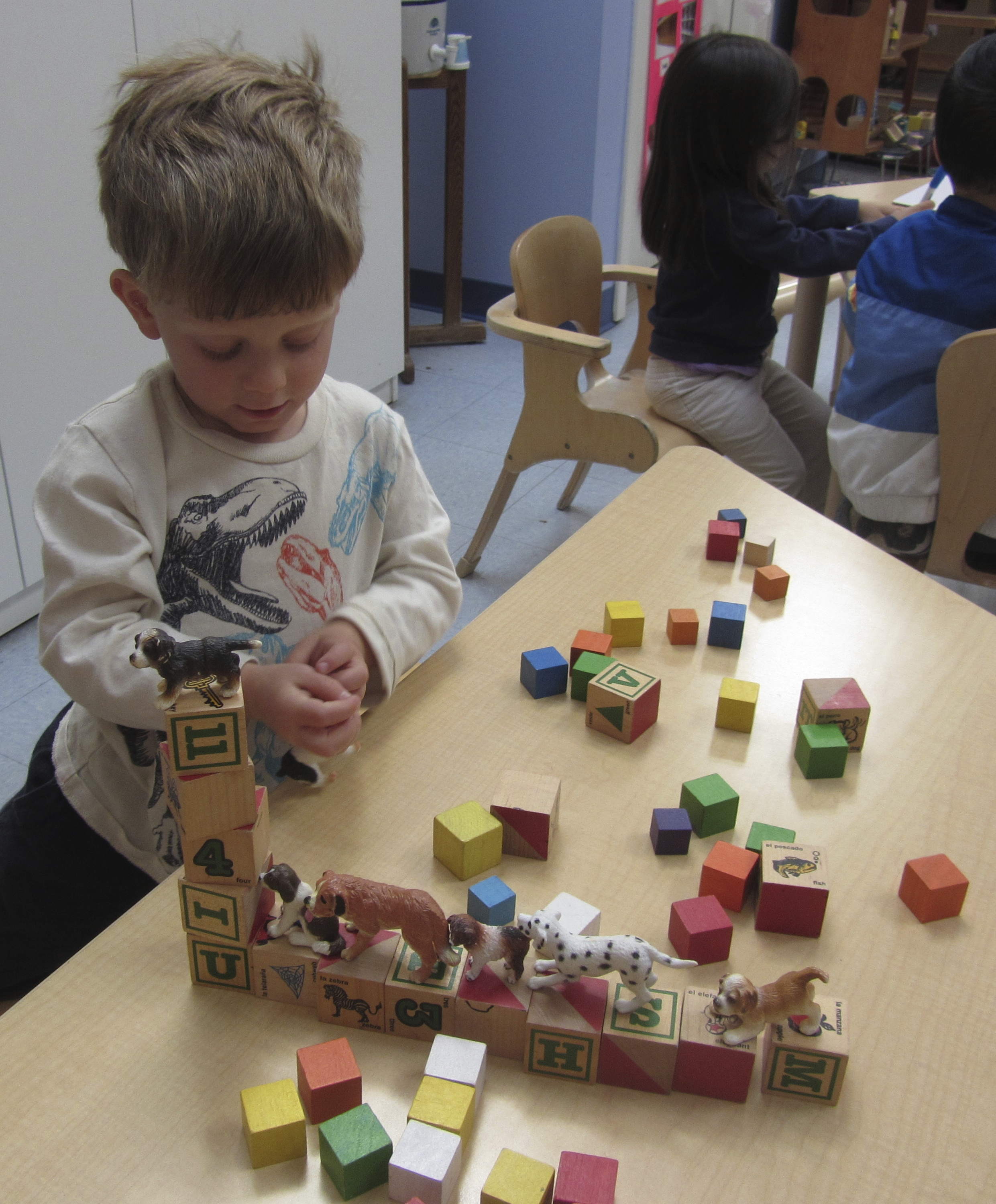 Working with small manipulatives, whether they are blocks, building toys, or small figures, spurs the imagination and tests developing fine motor skills.
