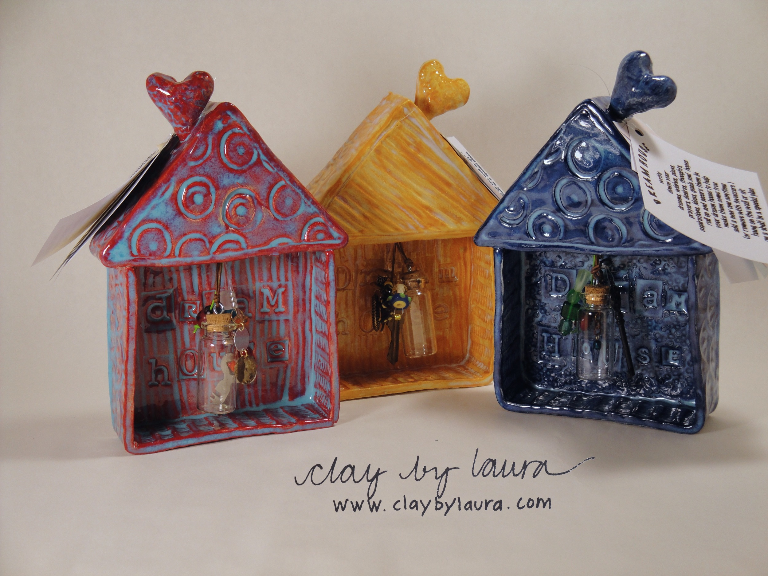 My Dream Houses embrace and hold your cherished thoughts on small bits of paper placed inside the glass bottle. Each unique home is embellished with beads, keys and found objects and can rest on a shelf or hang on a wall. Click on the photo to see what I have in stock!