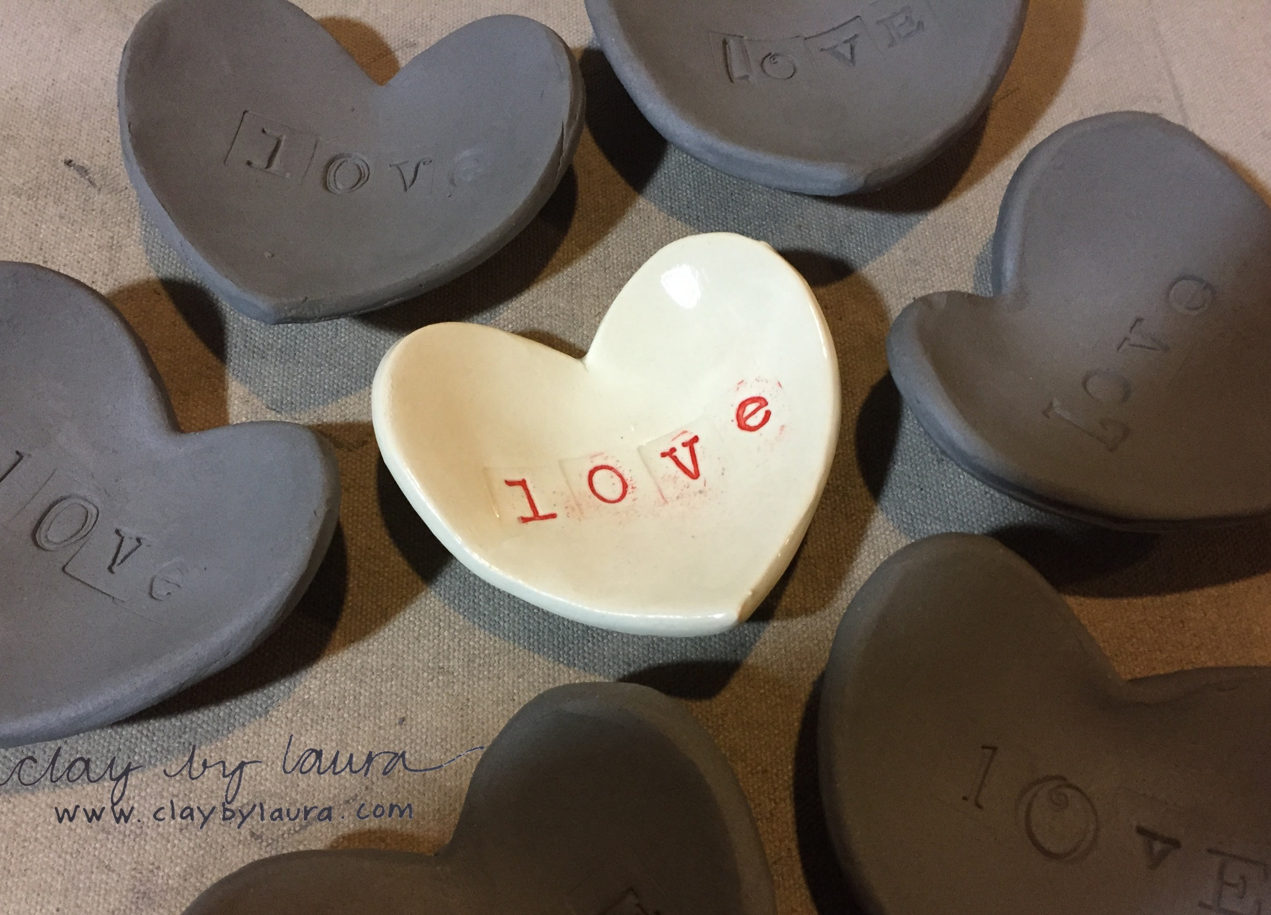 Small 'love' dishes awaiting their application of red underglaze.