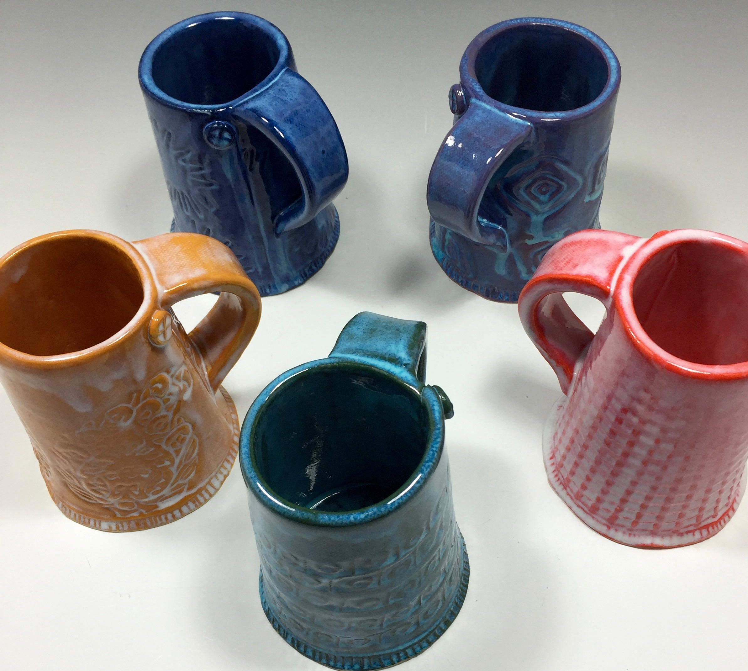 I've revised the shape of my mugs. These are narrow at the top and wide at the bottom. I still feature a seam line and button. The narrow top will help hold the temperature of a hot drink.