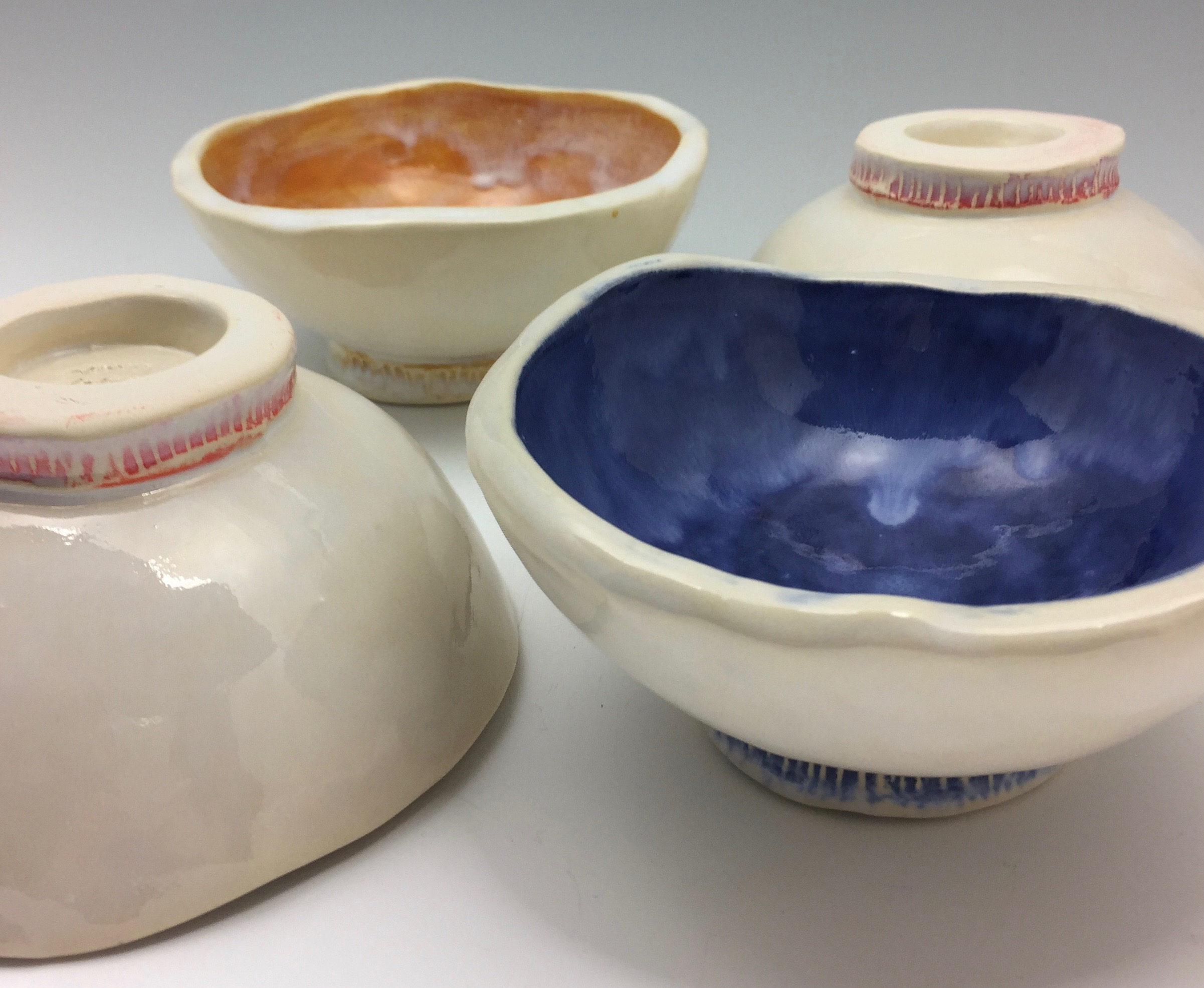 This group of bowls is accompanying a dinner set on its way to California. I experimented and accented each foot of the bowl with a pop of color. I like the results!