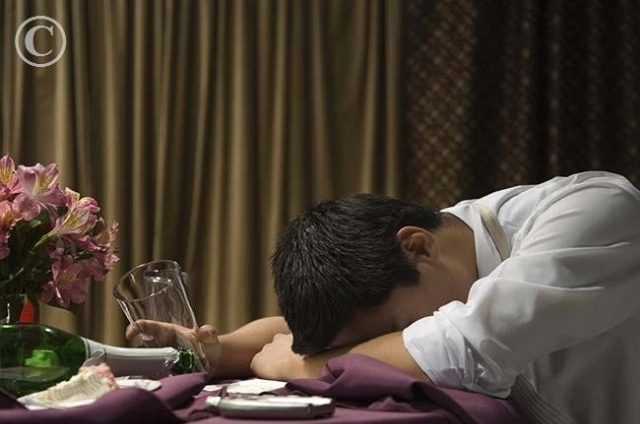 Asian_man_with_head_on_table_BLD057782.jpg