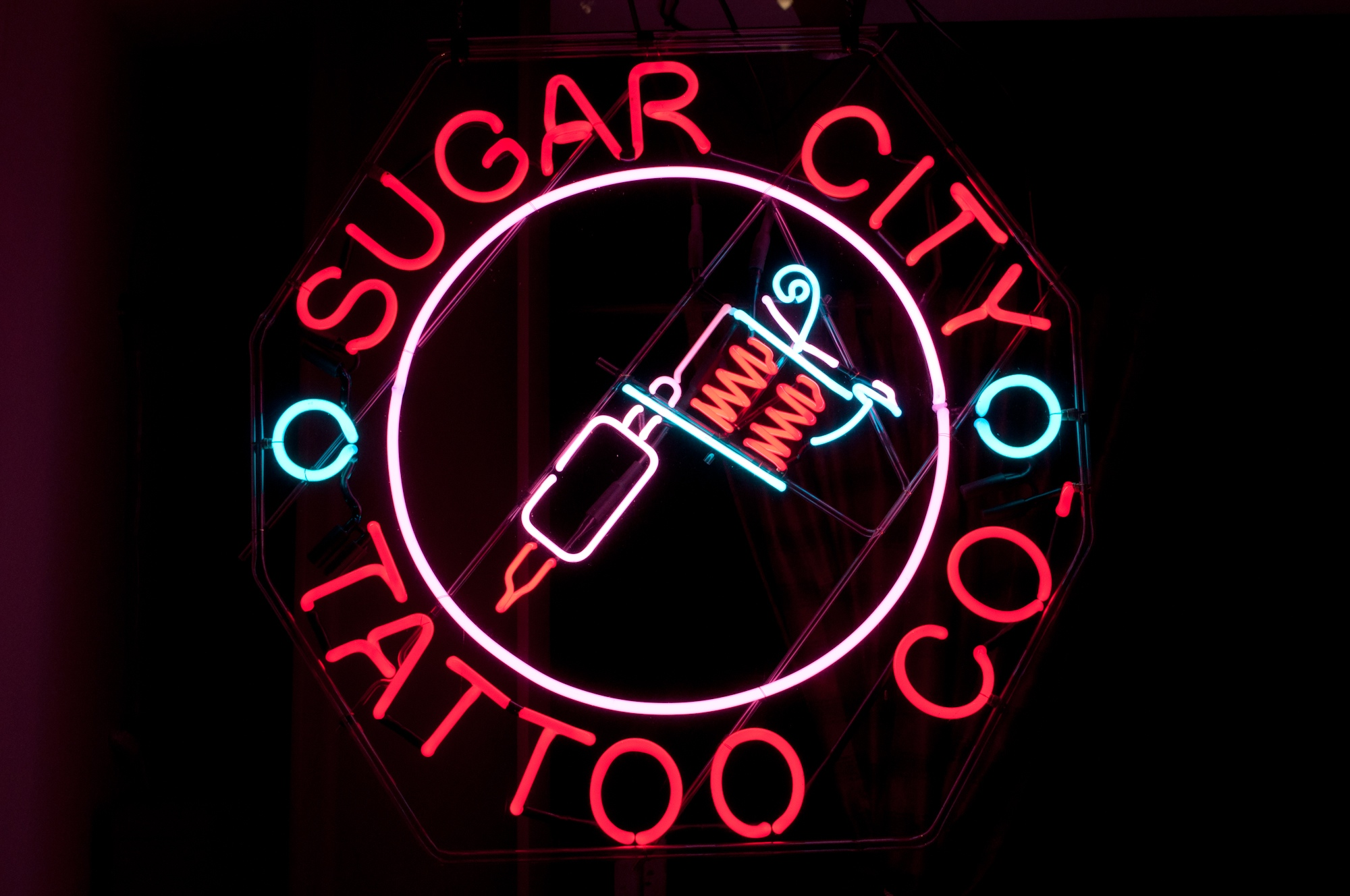 "Sugar City Tattoo, Crockett, CA, mounted on an old school, clear glass ""skeletal"" frame."