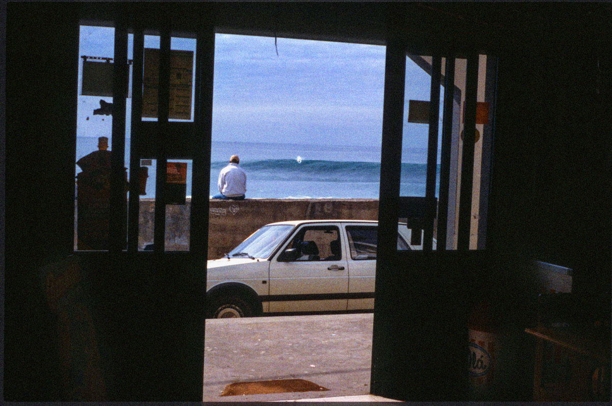 William Finnegan relaxes on the seawall at Paul do Mar while one of the Portuguese pro surfers gets the double overhead beach break to himself.