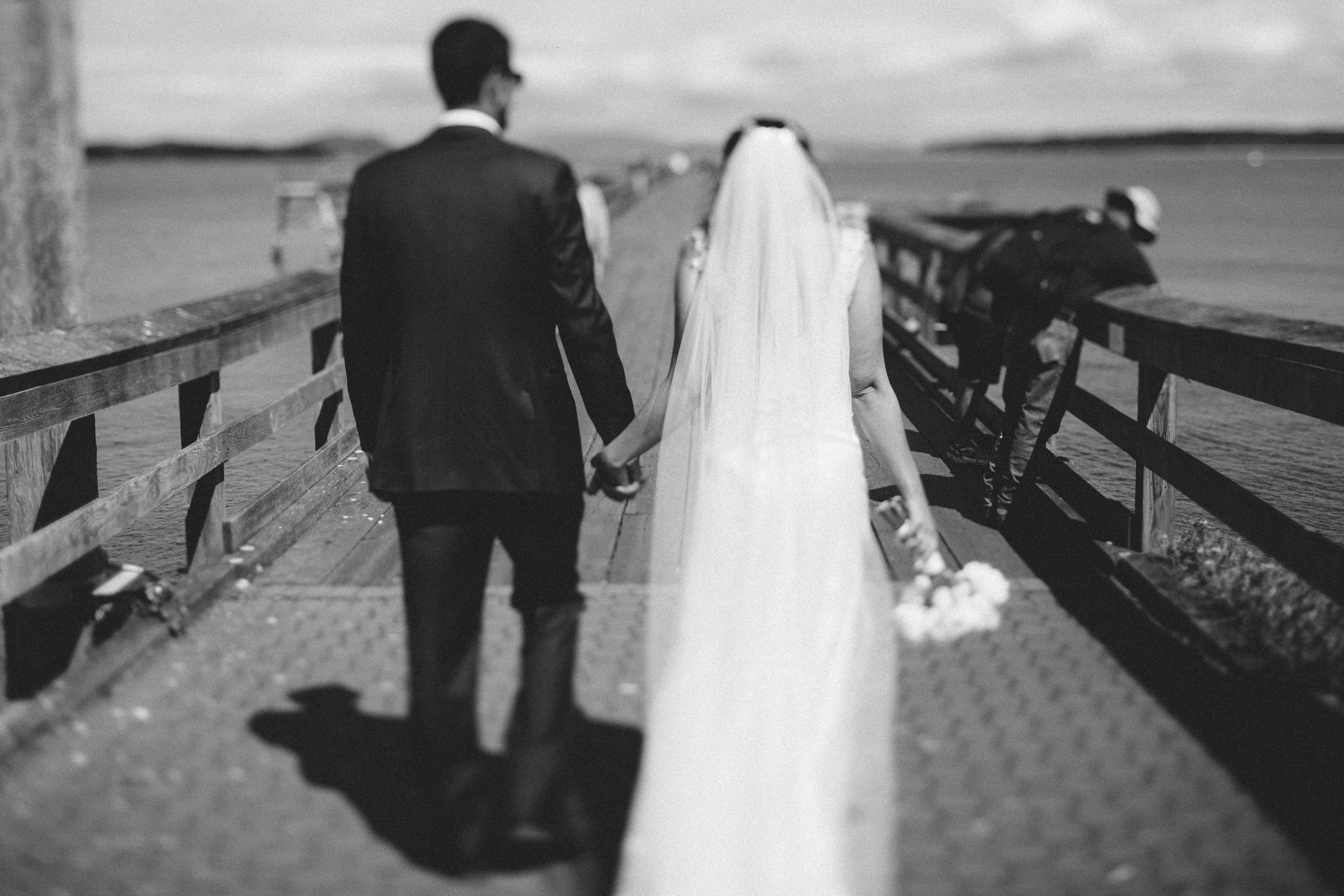 The groom holds her bride's hand Beach wedding Sea Cider Tofino Vancouver Island