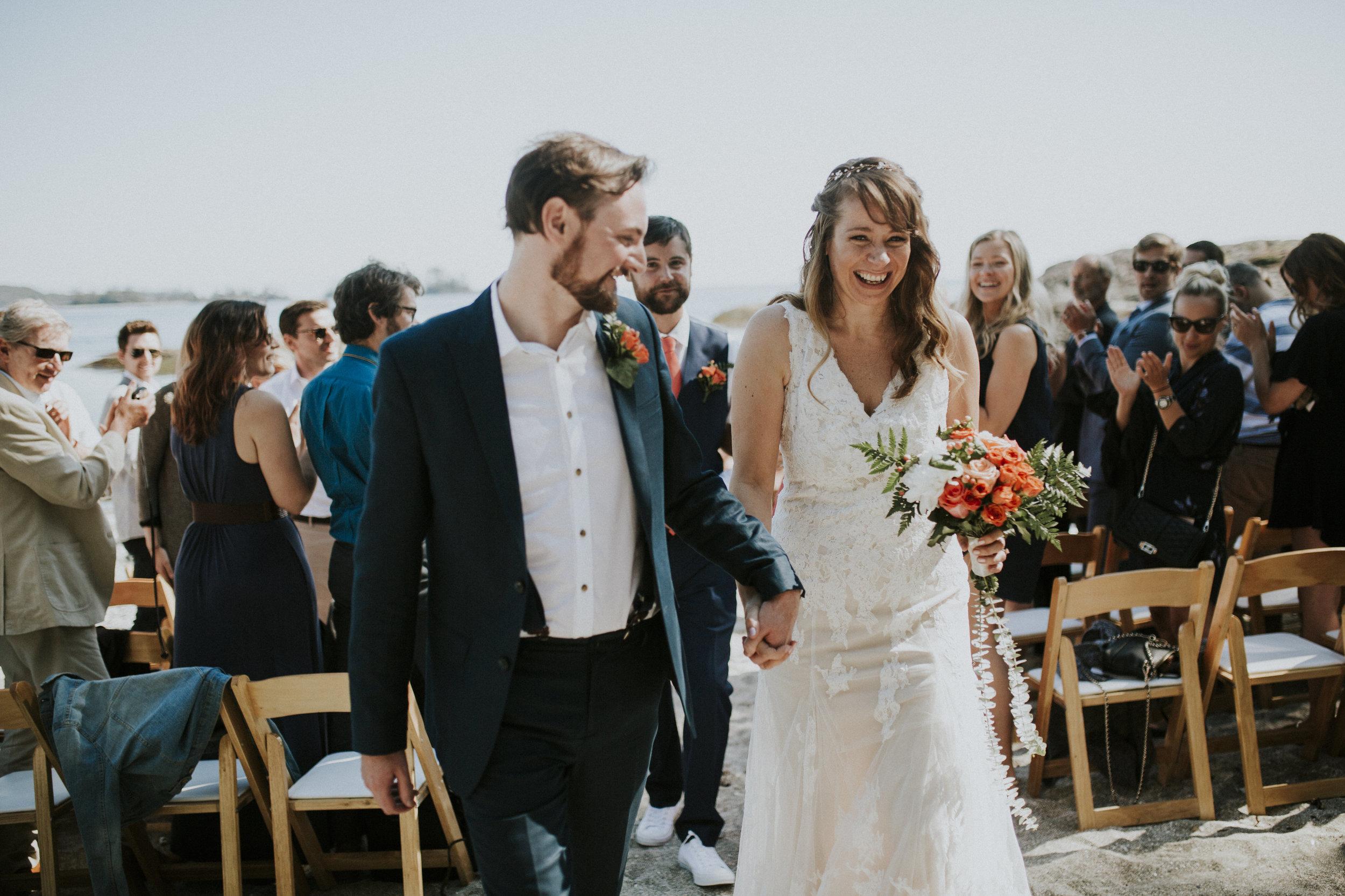 married couple walk down isle seashell beach tofino wedding