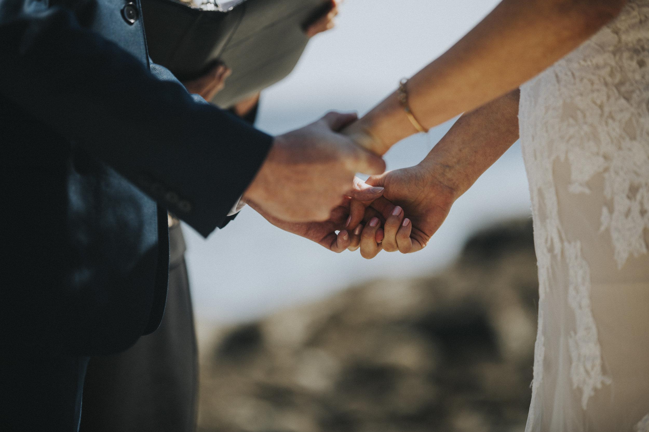 couple holds hands on beach wedding ceremony tofino wedding photographer