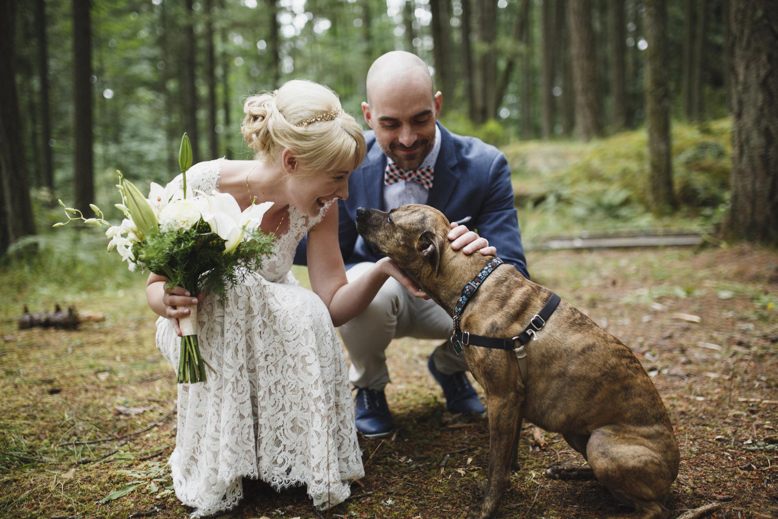 Newly wed couple playing with dog Forest wedding at King Francis Park Vancouver Island