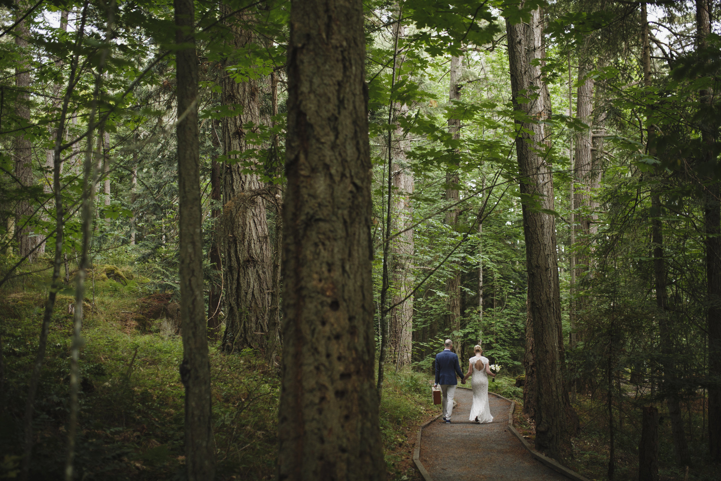Newly wed Bride and Groom walking Forest wedding in King Francis Park Vancouver Island