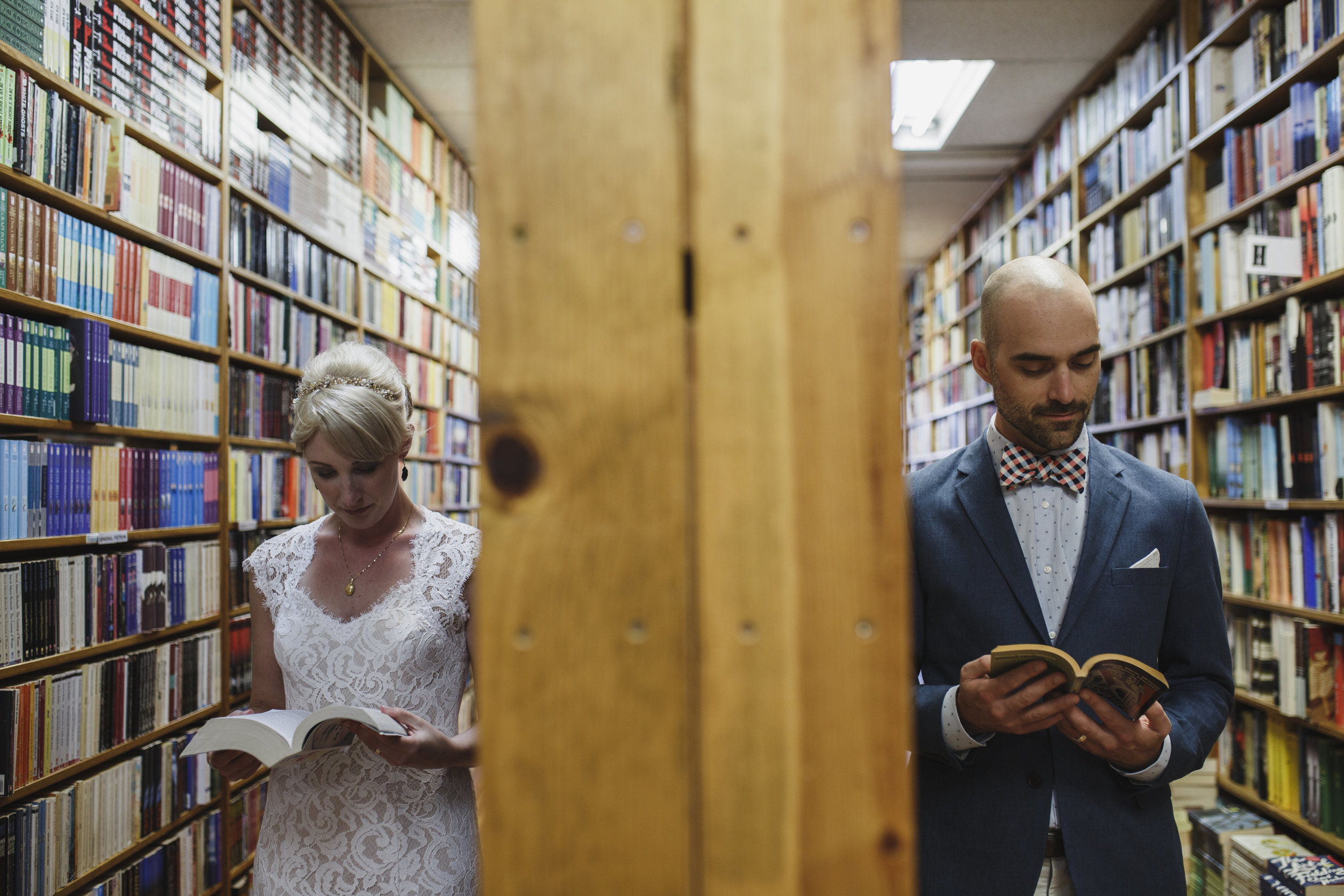 Bride and groom in a bookstore reading books The Guild wedding Vancouver Island