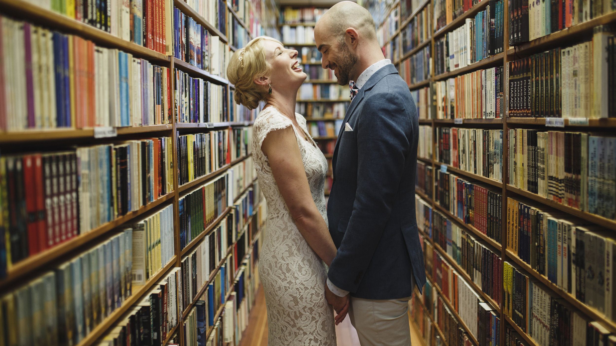 Bride and Groom in a bookstore laughing The Guild Wedding Vancouver Island