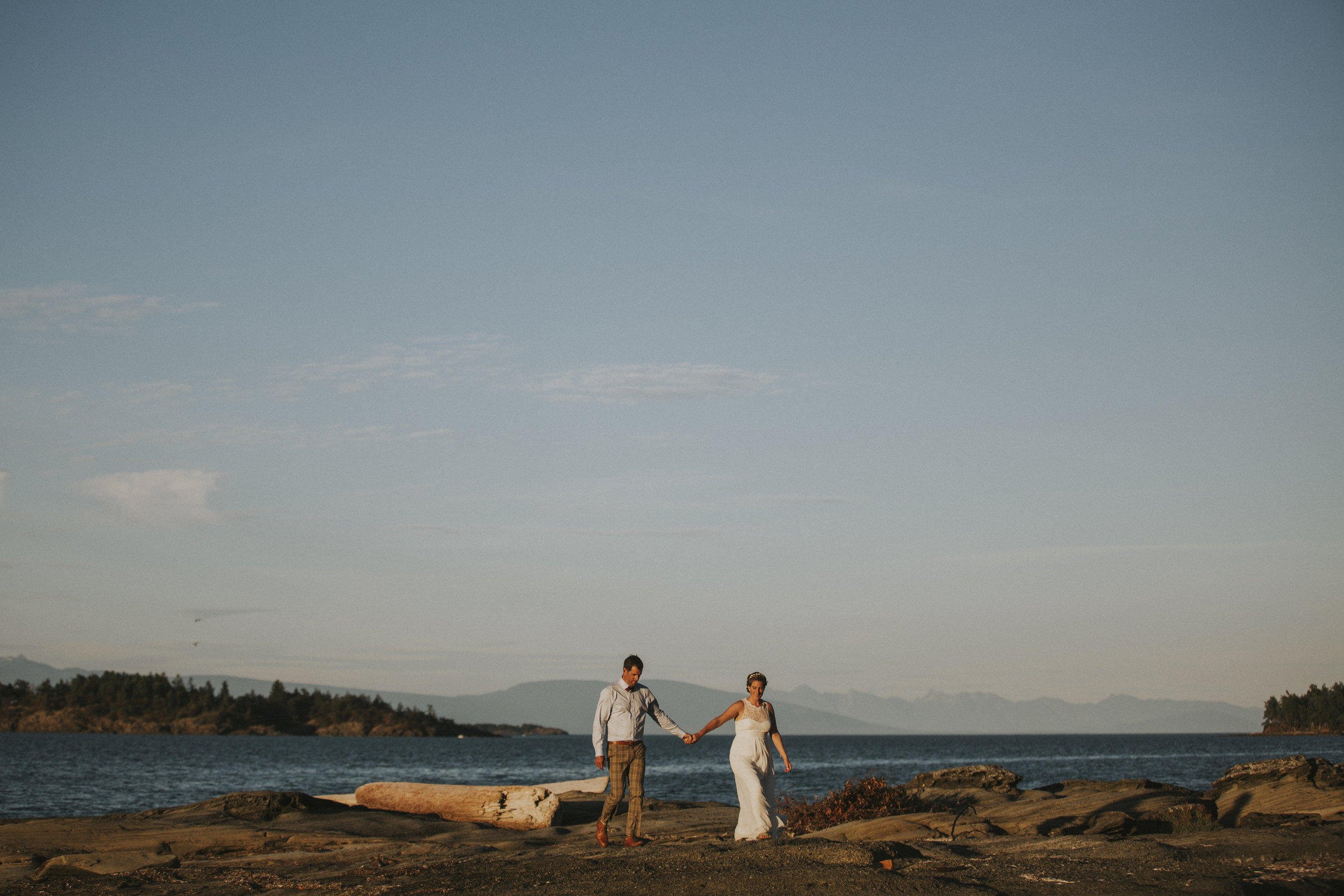 The newly wed Bride and Groom strolling while holding hands King Francis Park Forest Wedding ceremony Vancouver Island