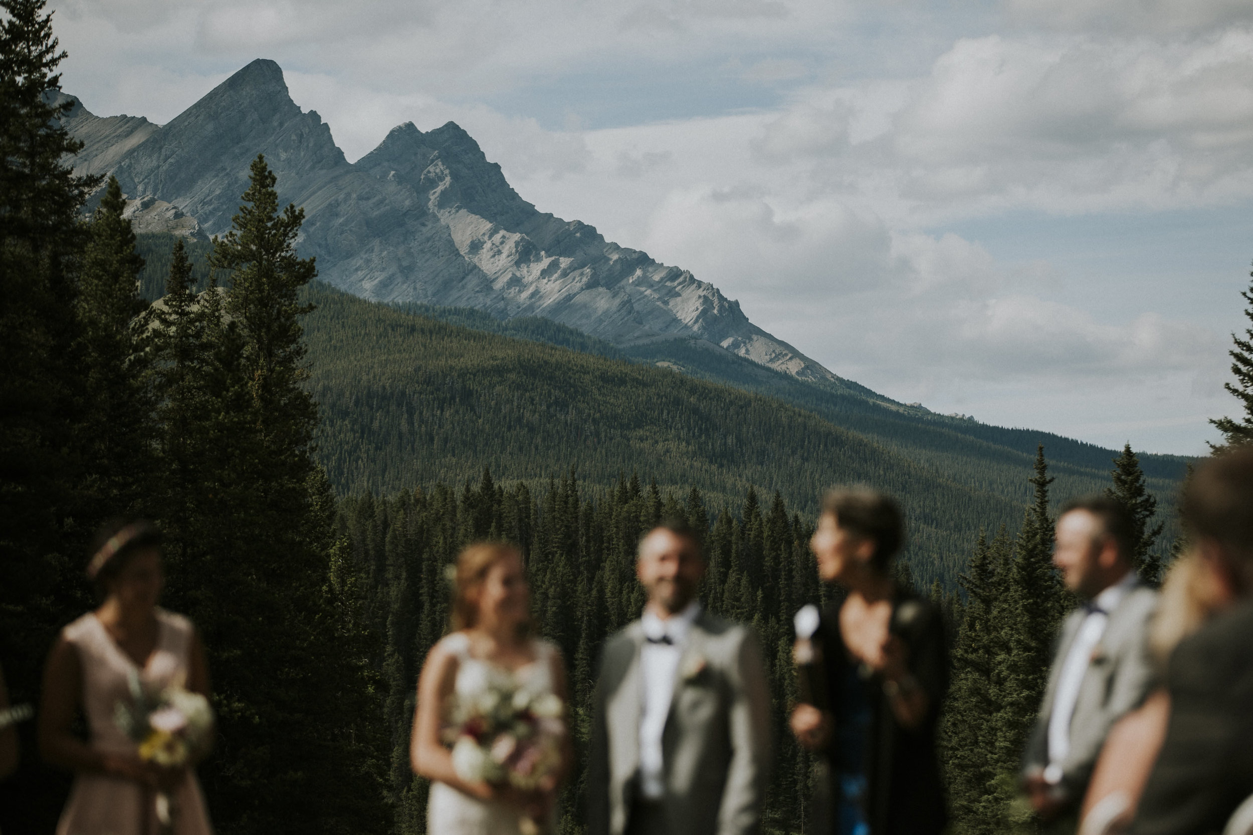 couple stands against mountains in the distance mt norquay banff