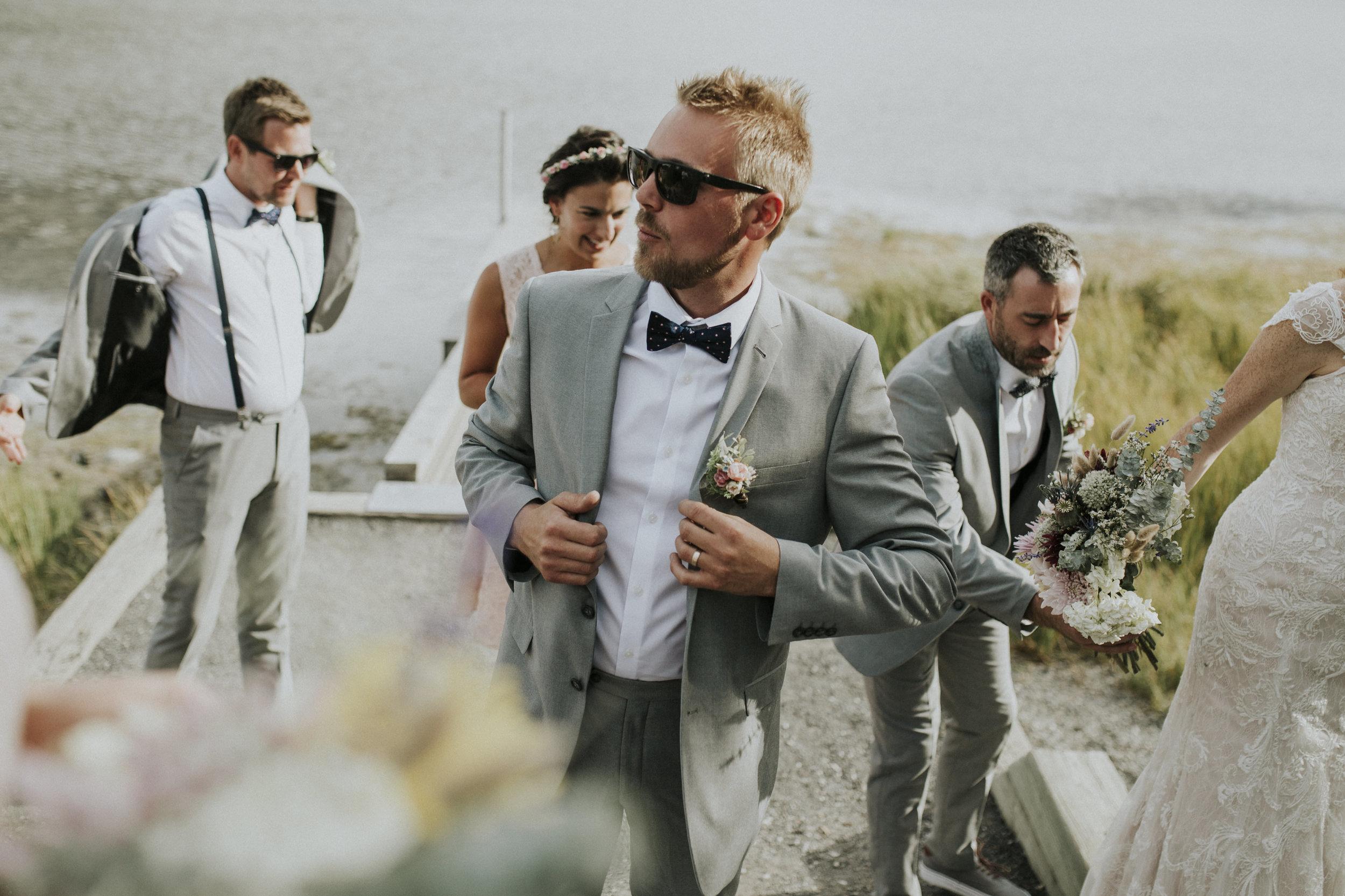 groomsman smiles at lake in banff