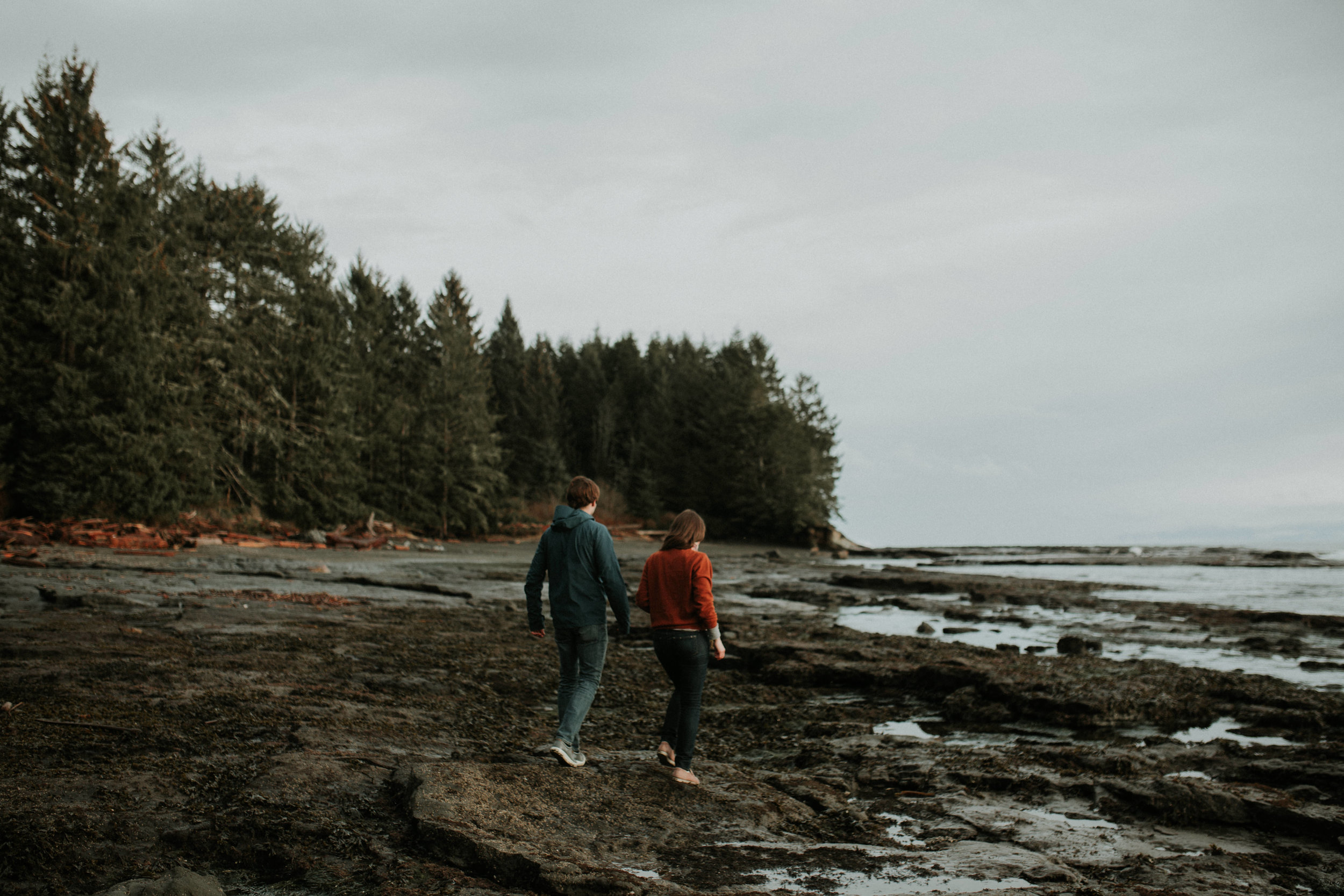 Couple walking along the shoreline Beach Engagement Botanical Beach Vancouver Island