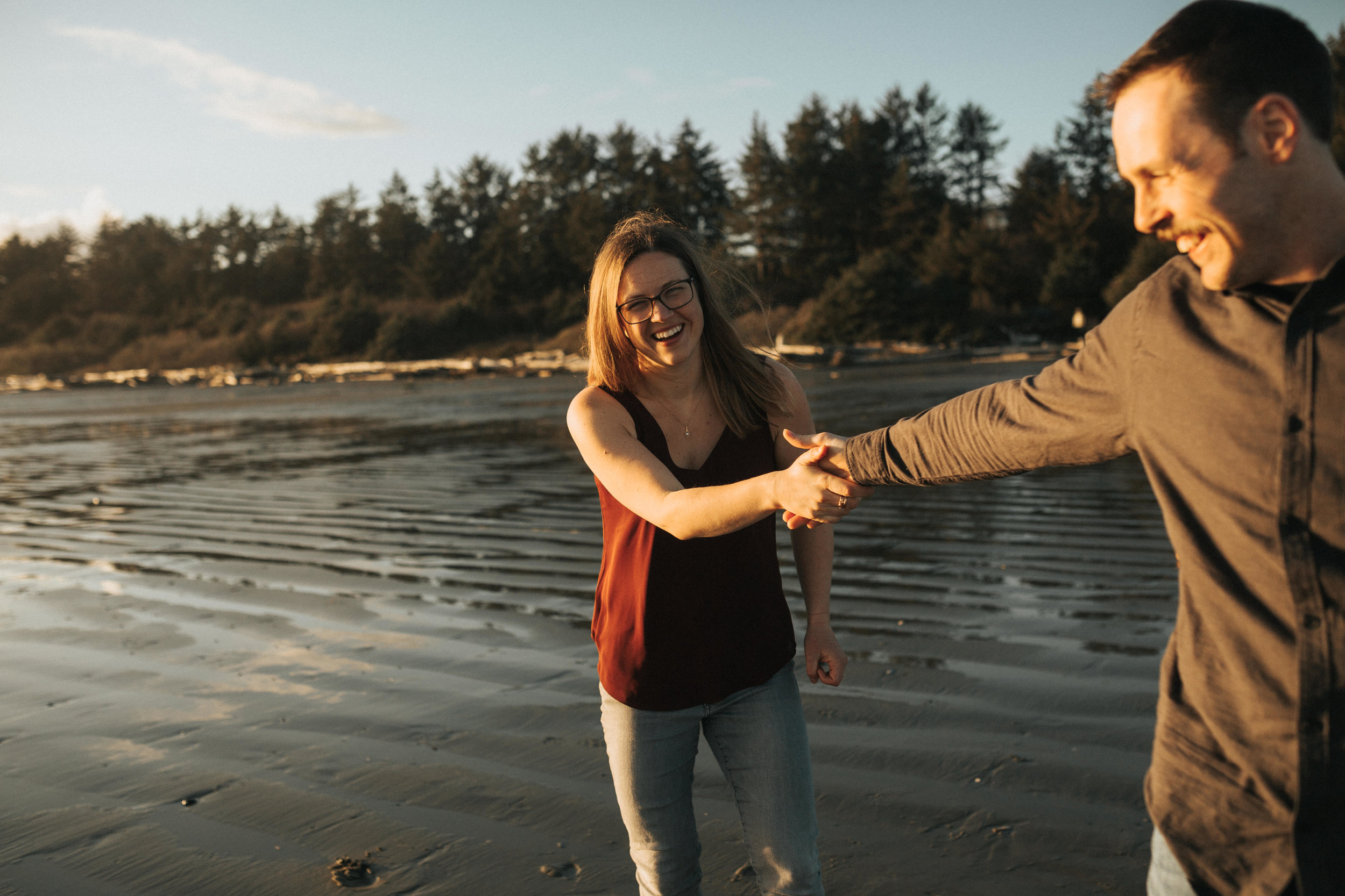 Couple holding hands laughing on Long Beach, Tofino, Vancouver Island.