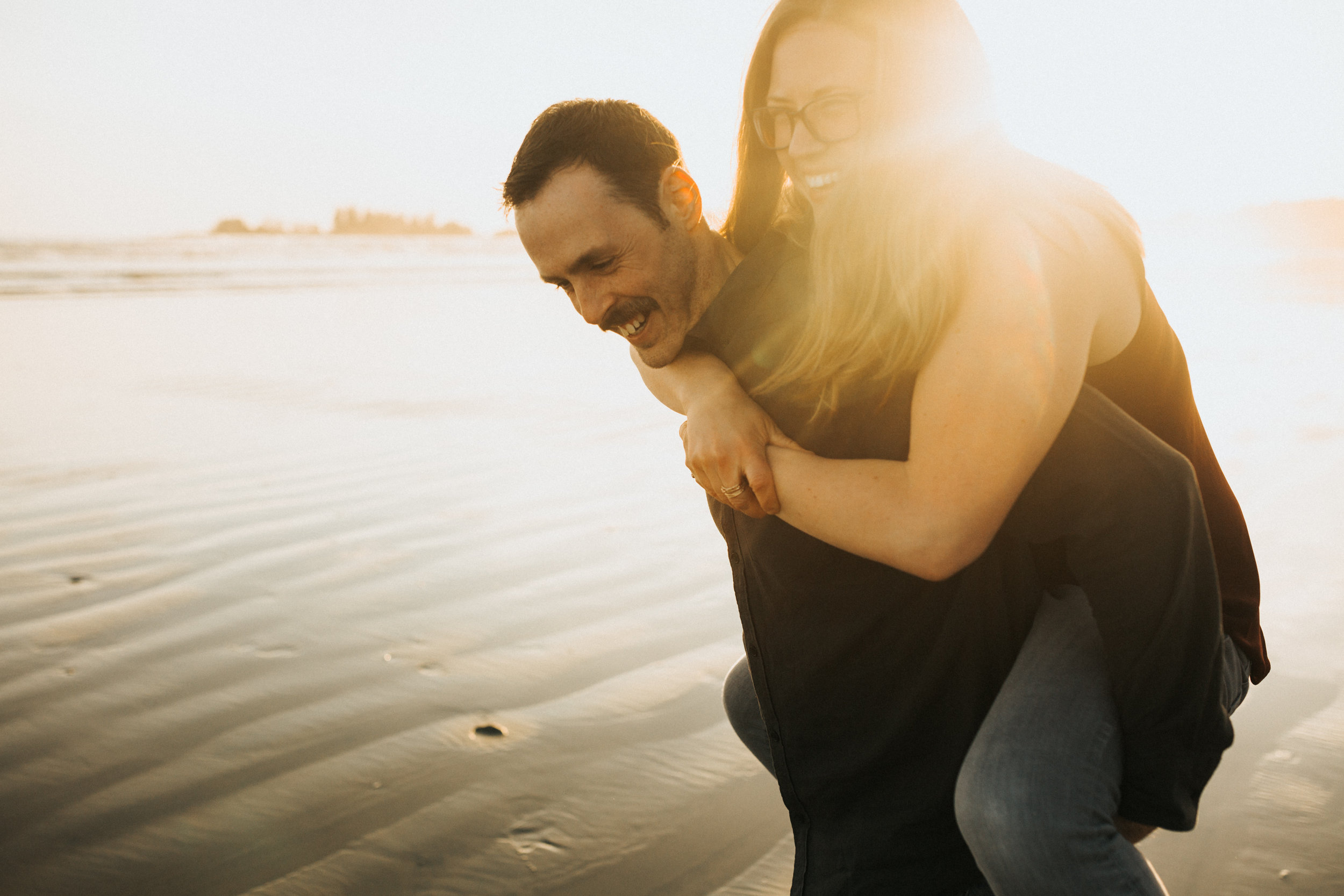 Girl getting a piggy-back from her fiancé, on Long Beach, Tofino, Vancouver Island at sunset