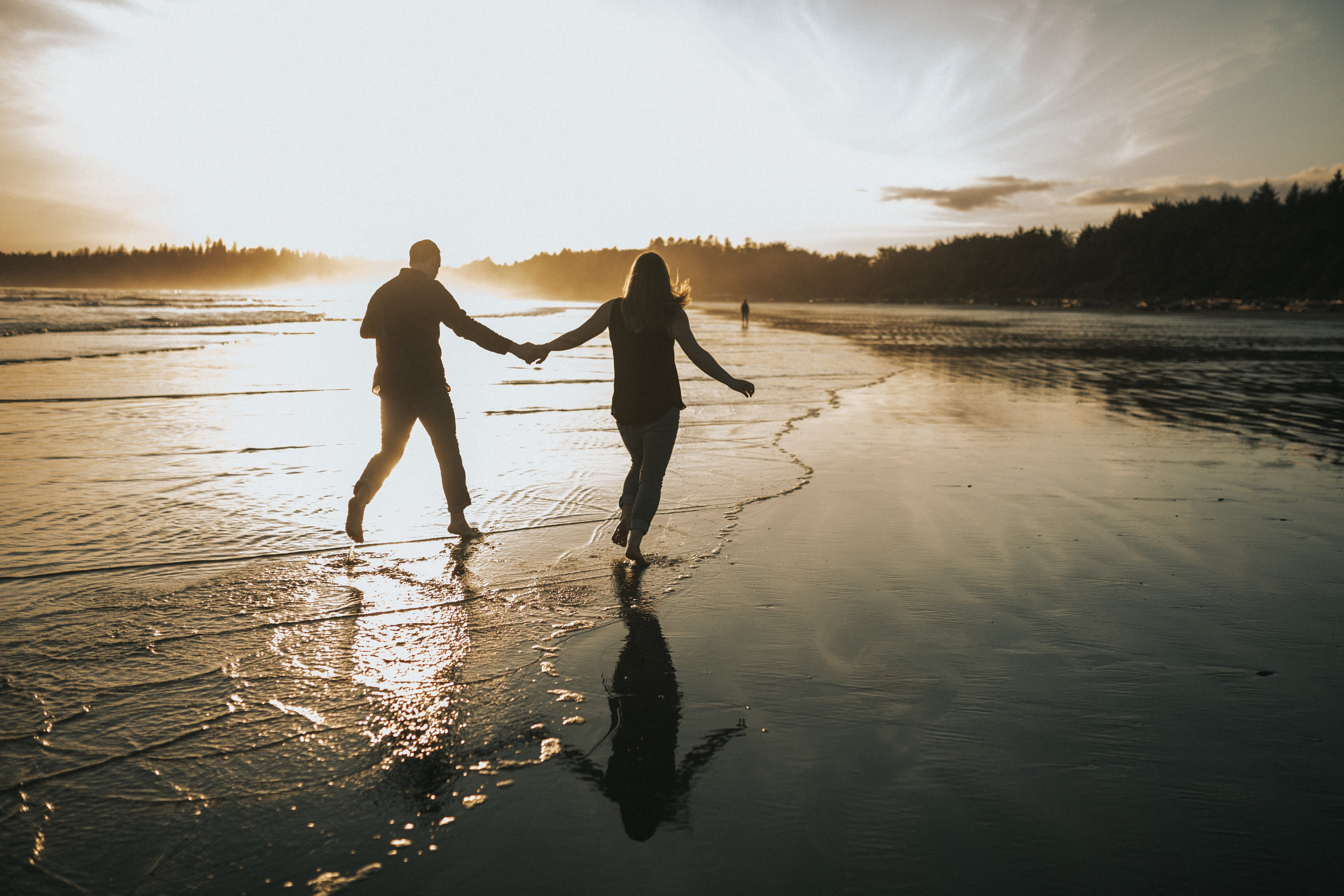 Couple walking through the water on Long Beach, in Tofino, Vancouver Island.