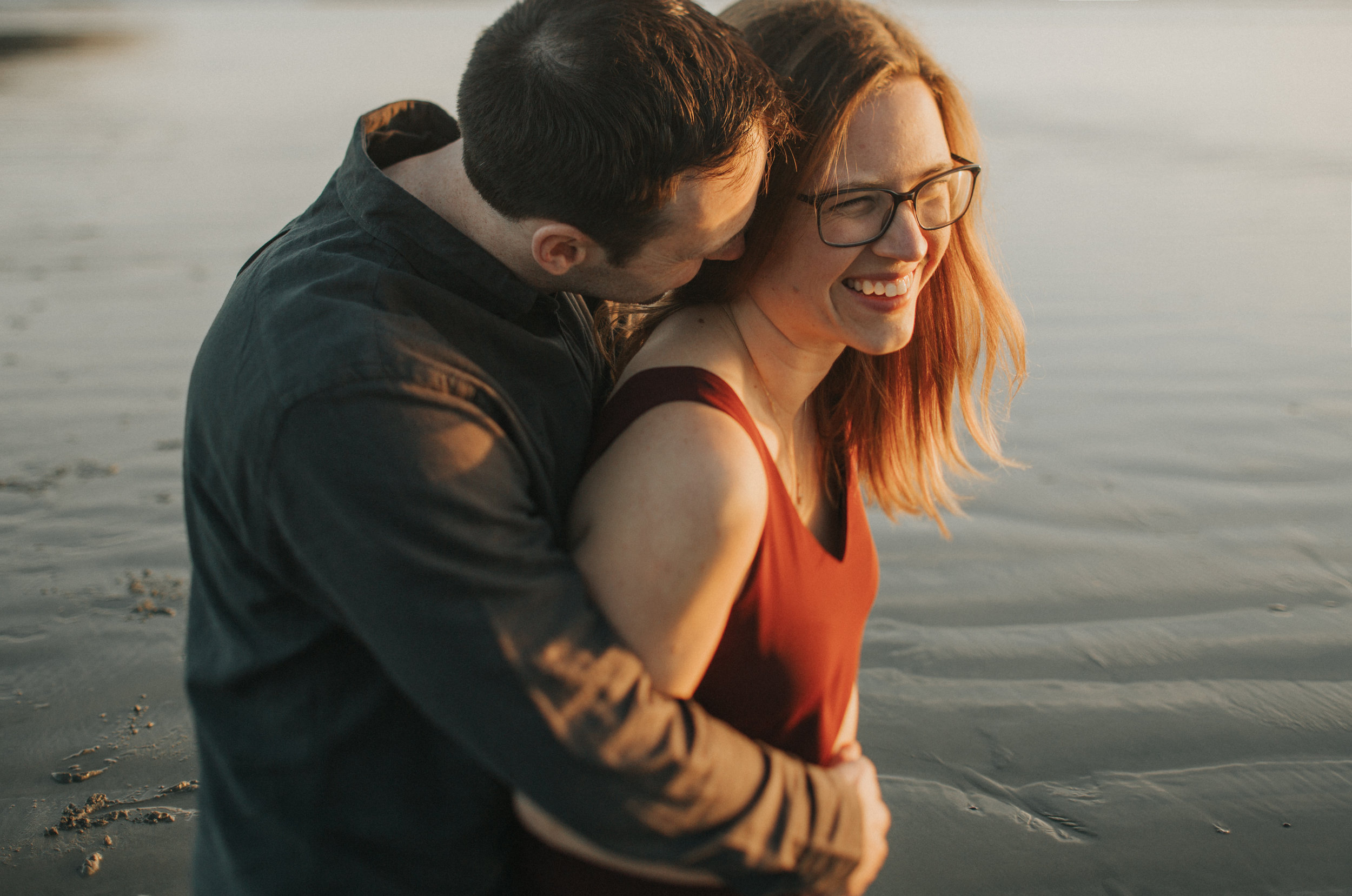 Couple laughing and hugging on Long Beach, Tofino