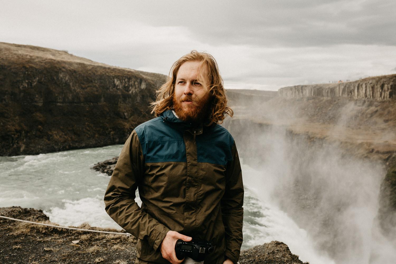 man stands near edge of gullfoss waterfall iceland
