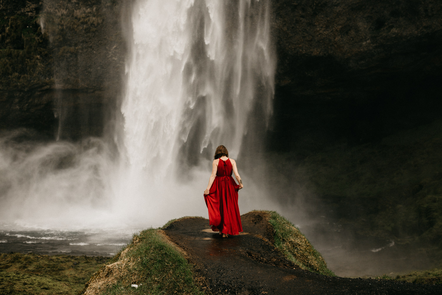 women in red dress at waterfall iceland