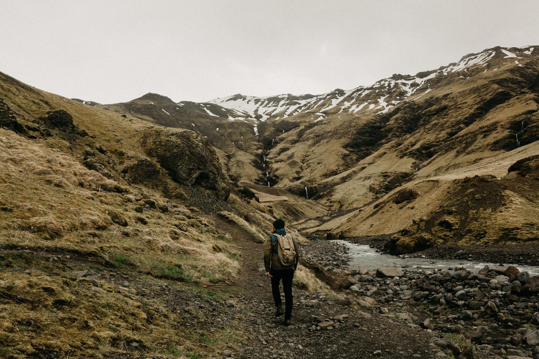 man hikes through hills in iceland