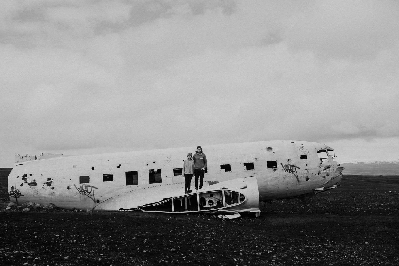 couple stands on crashed plane iceland vik