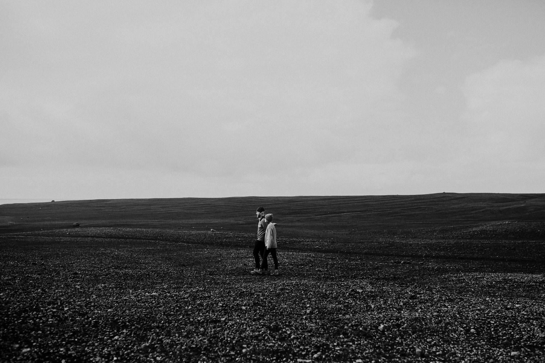 couple walks on black rocks iceland
