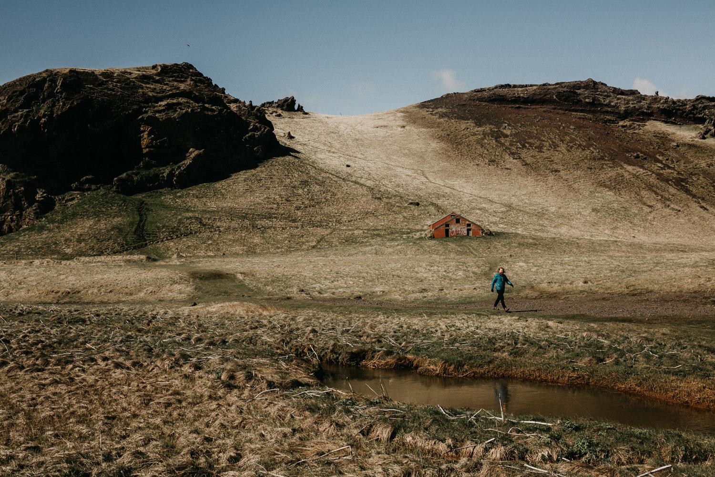 man walking hills vik iceland