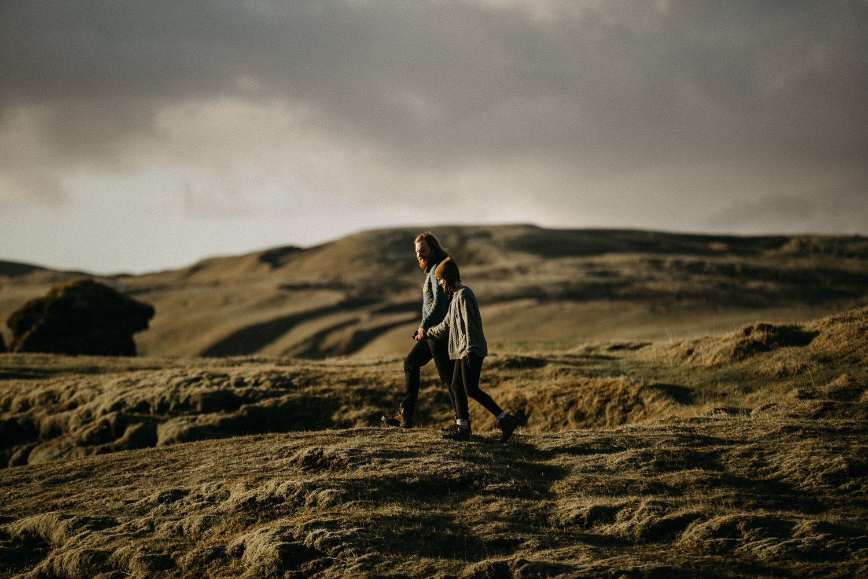 couple walks along Fjaðrárgljúfur canyon