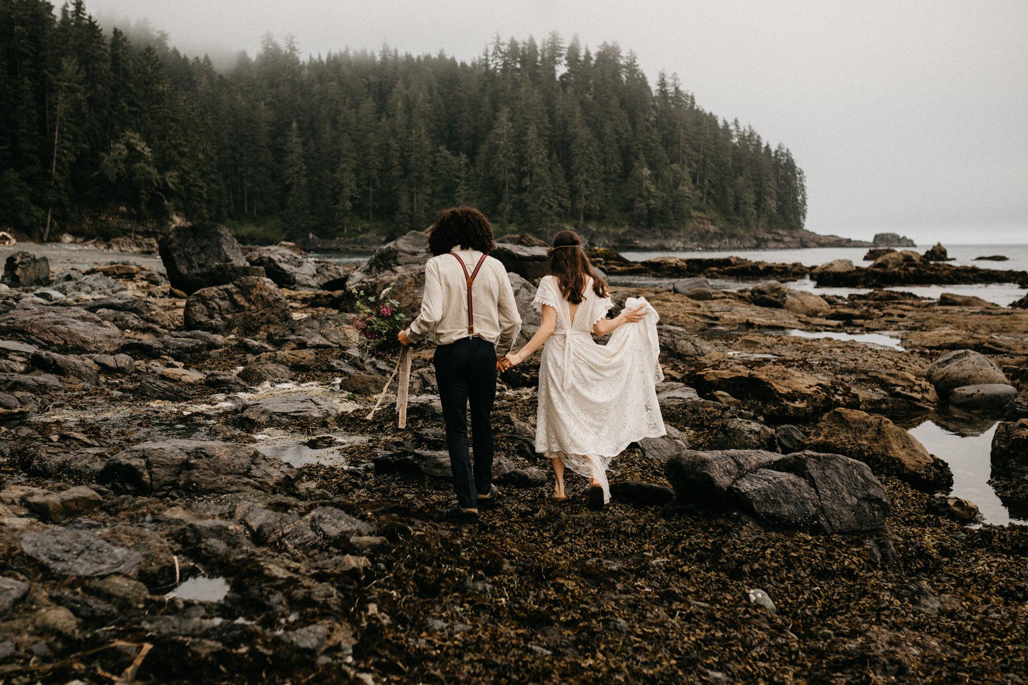 Couple walks along the shoreline Sombrio Beach Vancouver Island