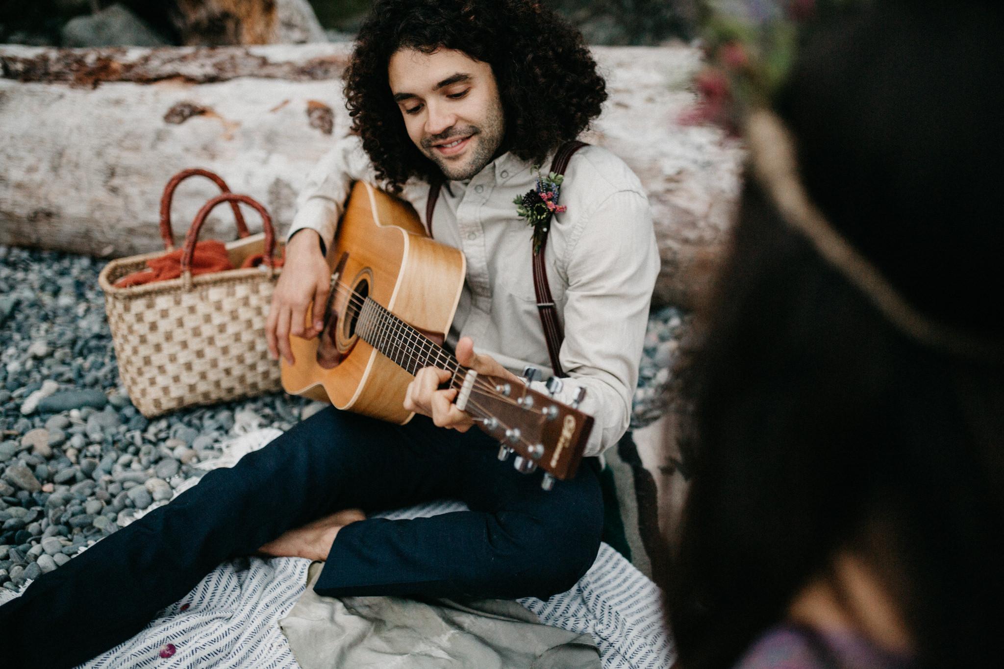 Groom plays guitar for his Bride Sombrio Beach elopement Vancouver Island