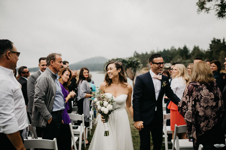 Newly wed Bride and Groom walk down isle Galiano Inn Beach Wedding Ceremony