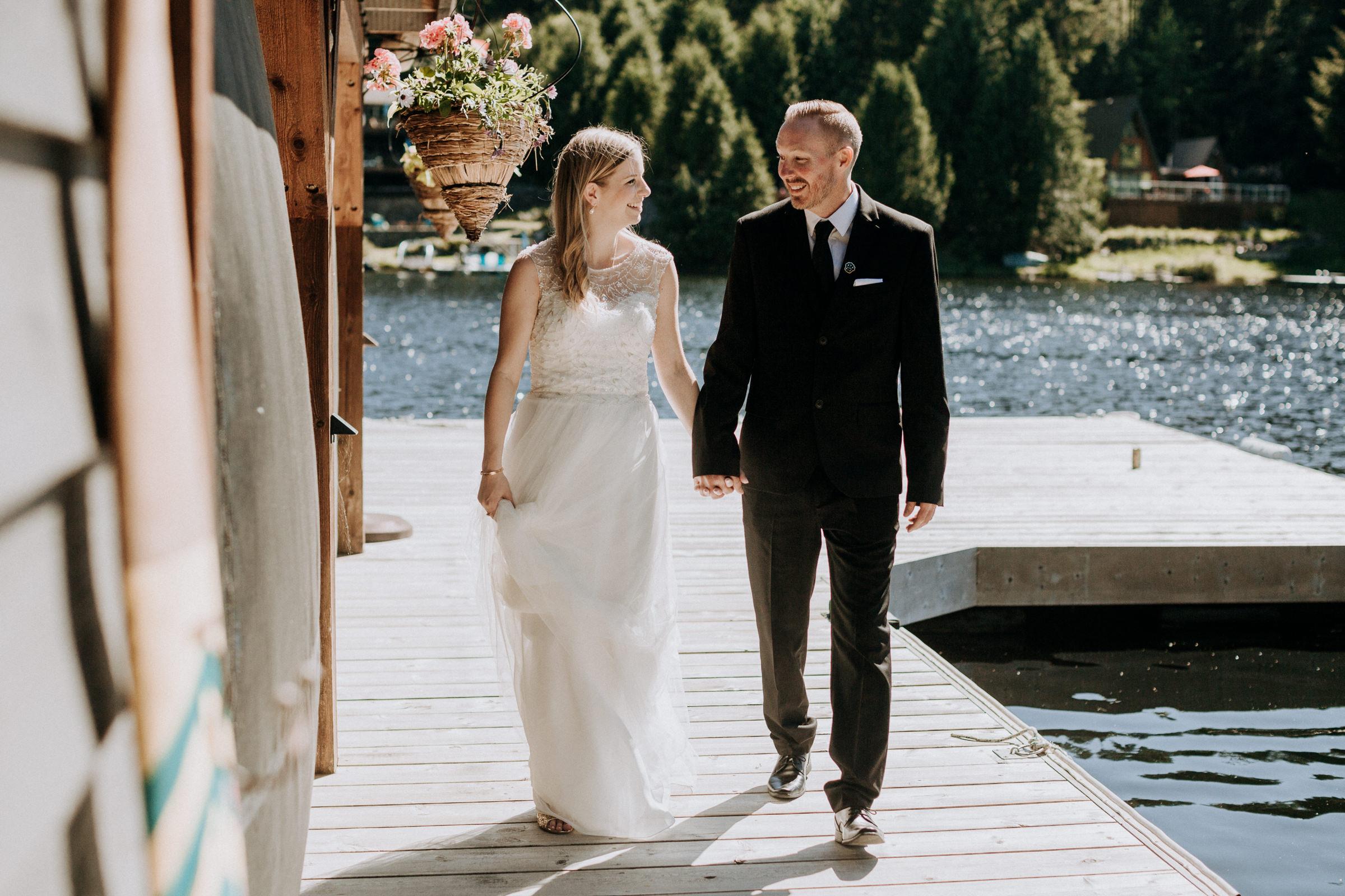 bride and groom walk on dock vancouver island wedding photographer