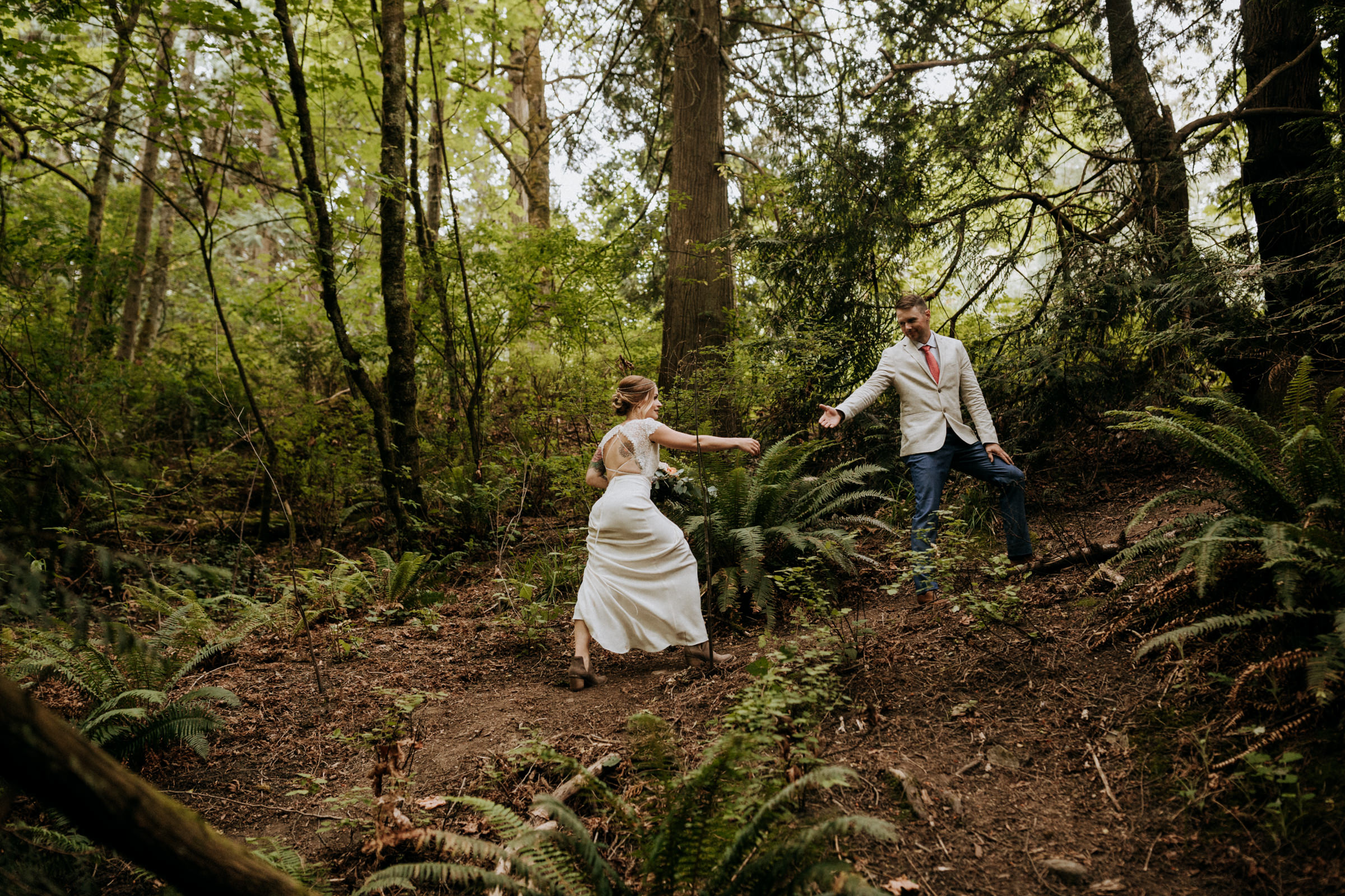 groom helps bride up forest hill Vancouver Island Elopement Photographer
