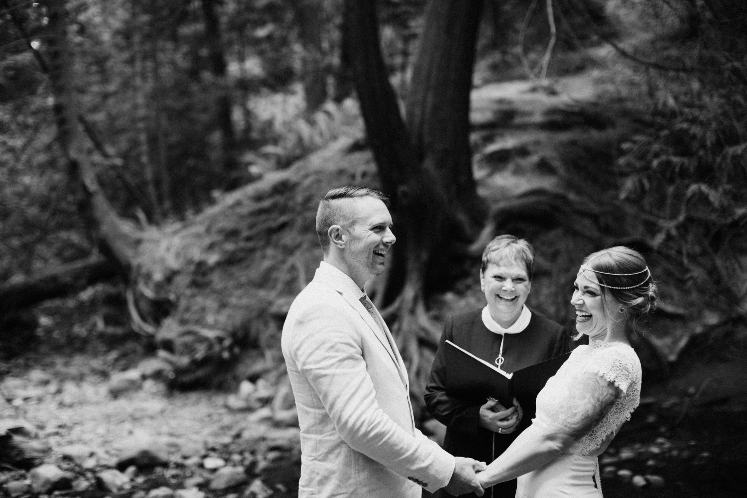 bride and groom hold hands at riverbed elopement ceremony vancouver island