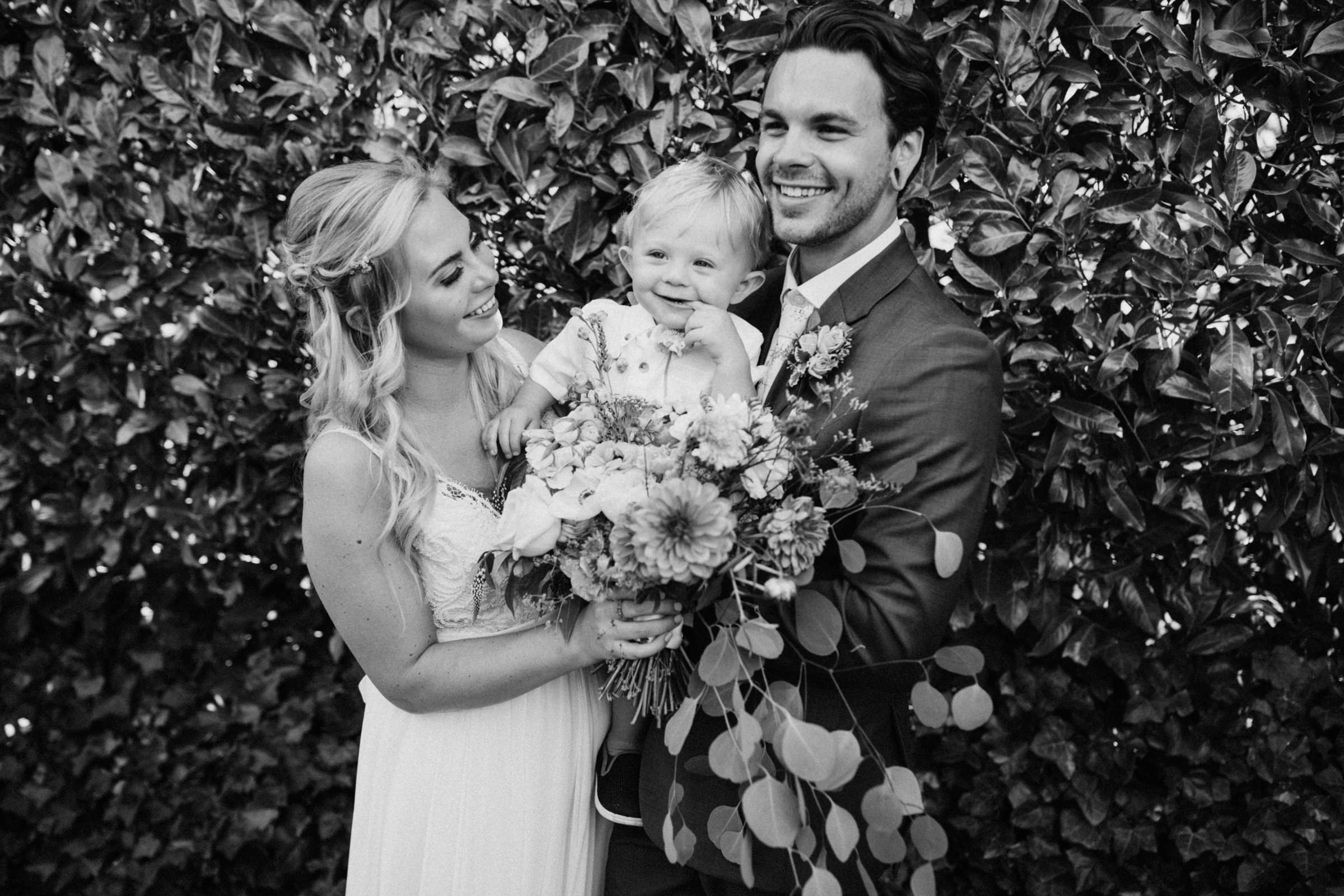 couples smiles with their boy West Vancouver backyard wedding photographer