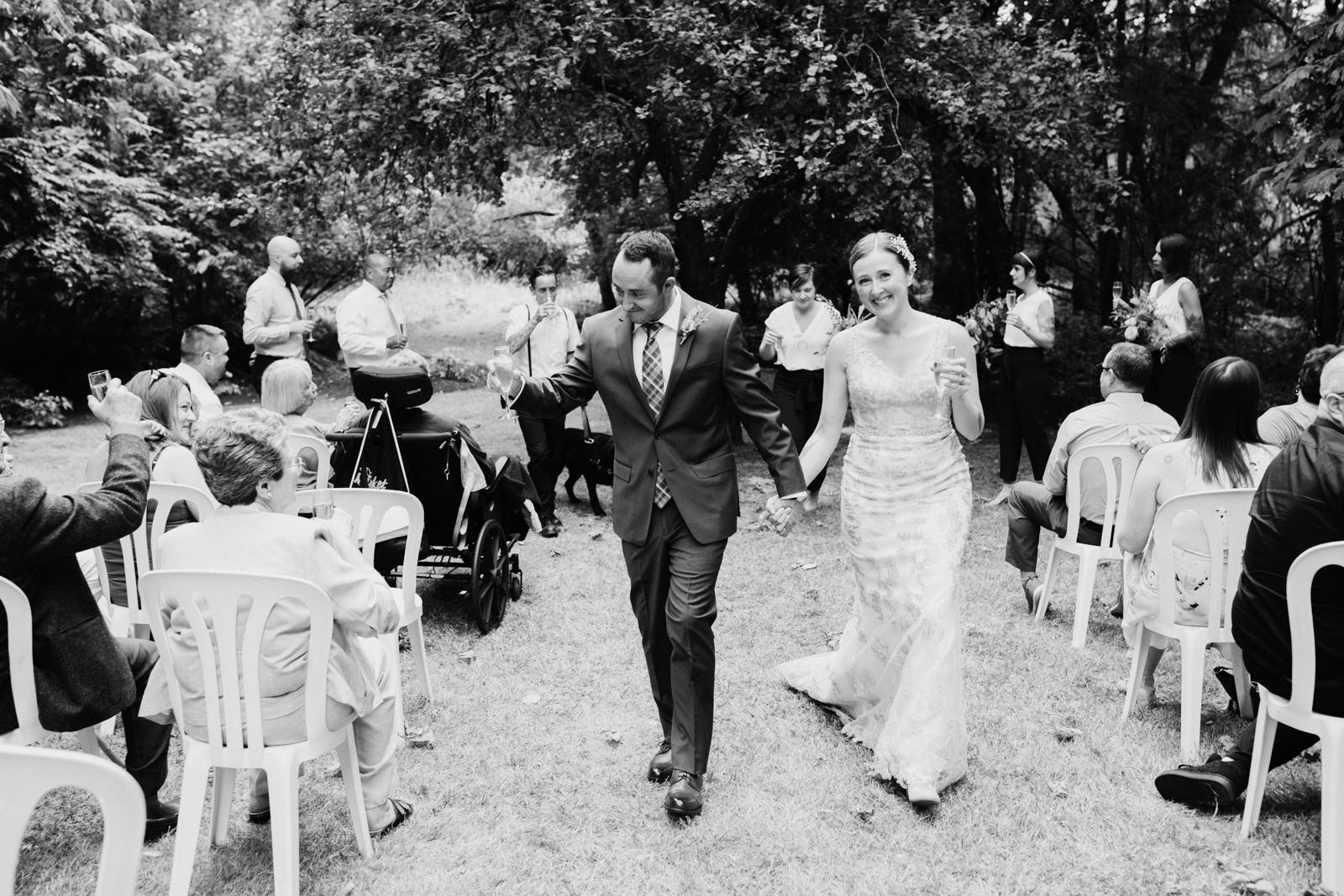 bride and groom walk down isle intimate Victoria wedding