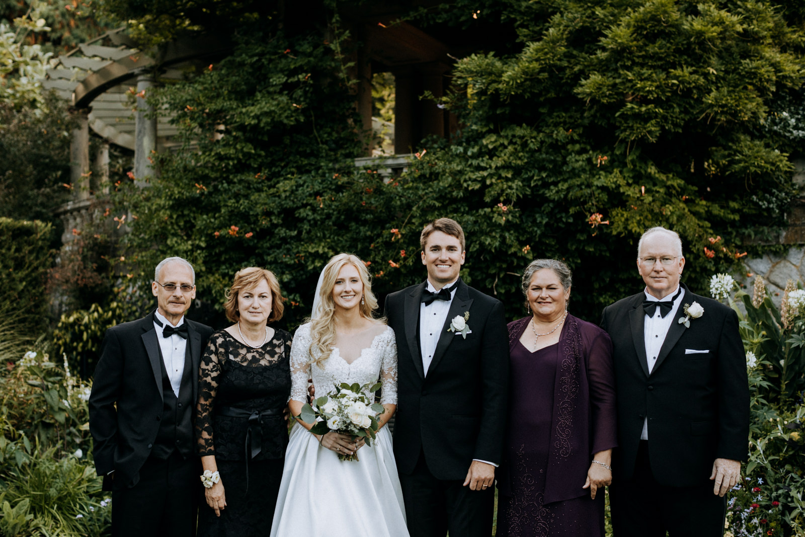 Couple poses with family at Hatley Castle wedding