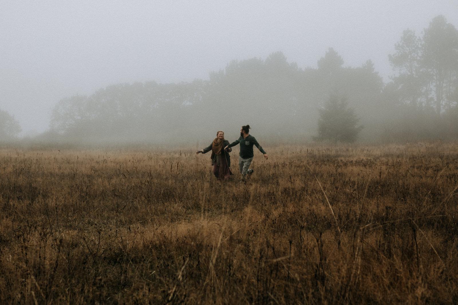 couple runs through fog Beacon Hill - Vancouver Island Elopement Photographer