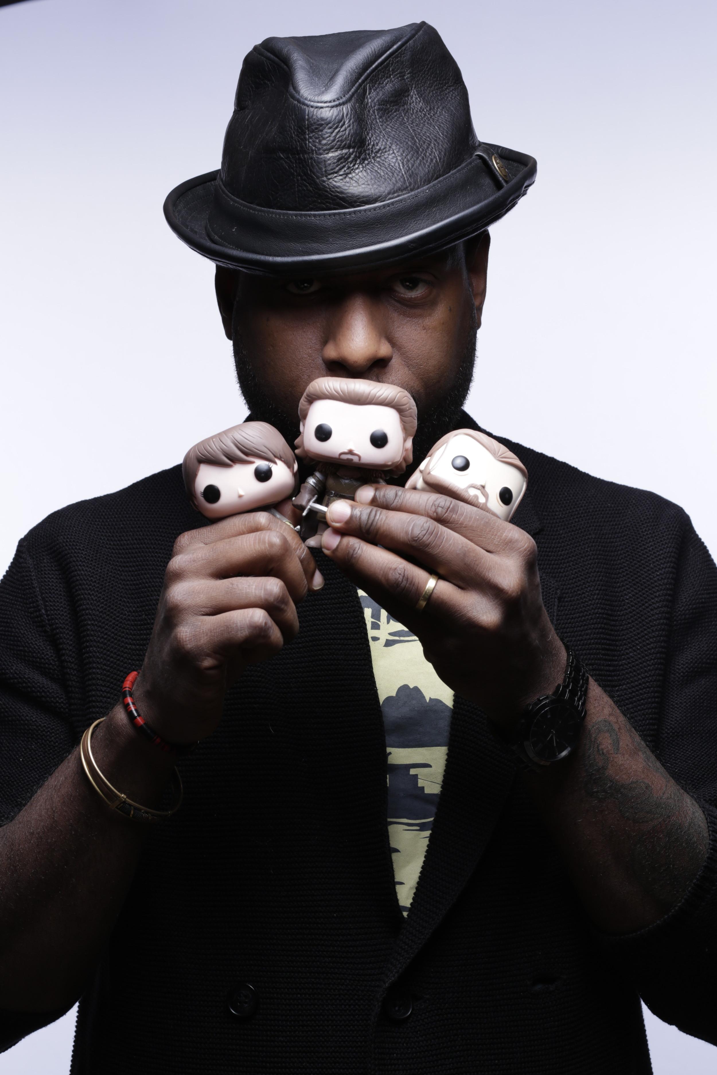 Talib Kweli poses with the GOT Funko dolls.