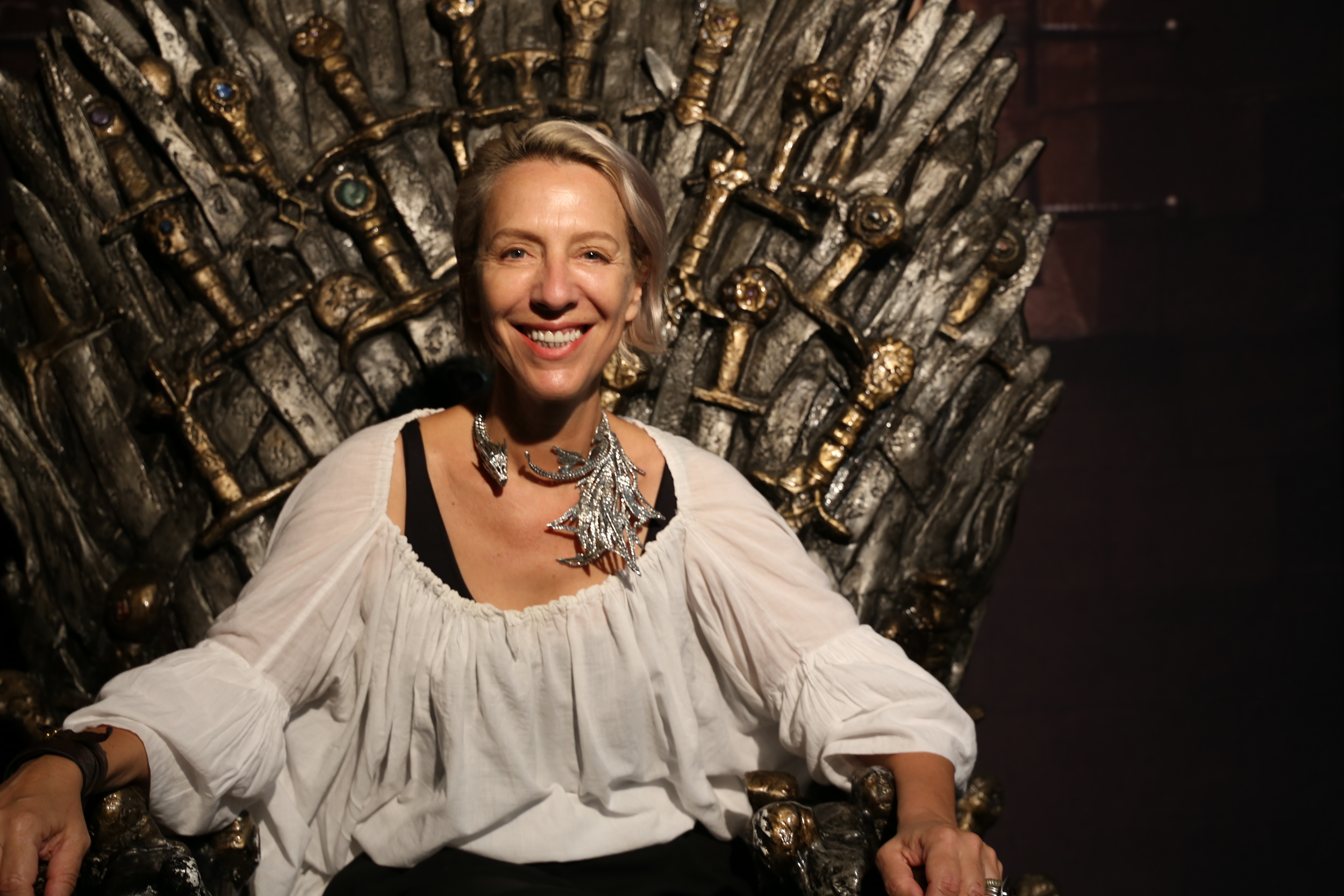 Costume designer Michele Clapton sits on the Iron Throne at SDCC.