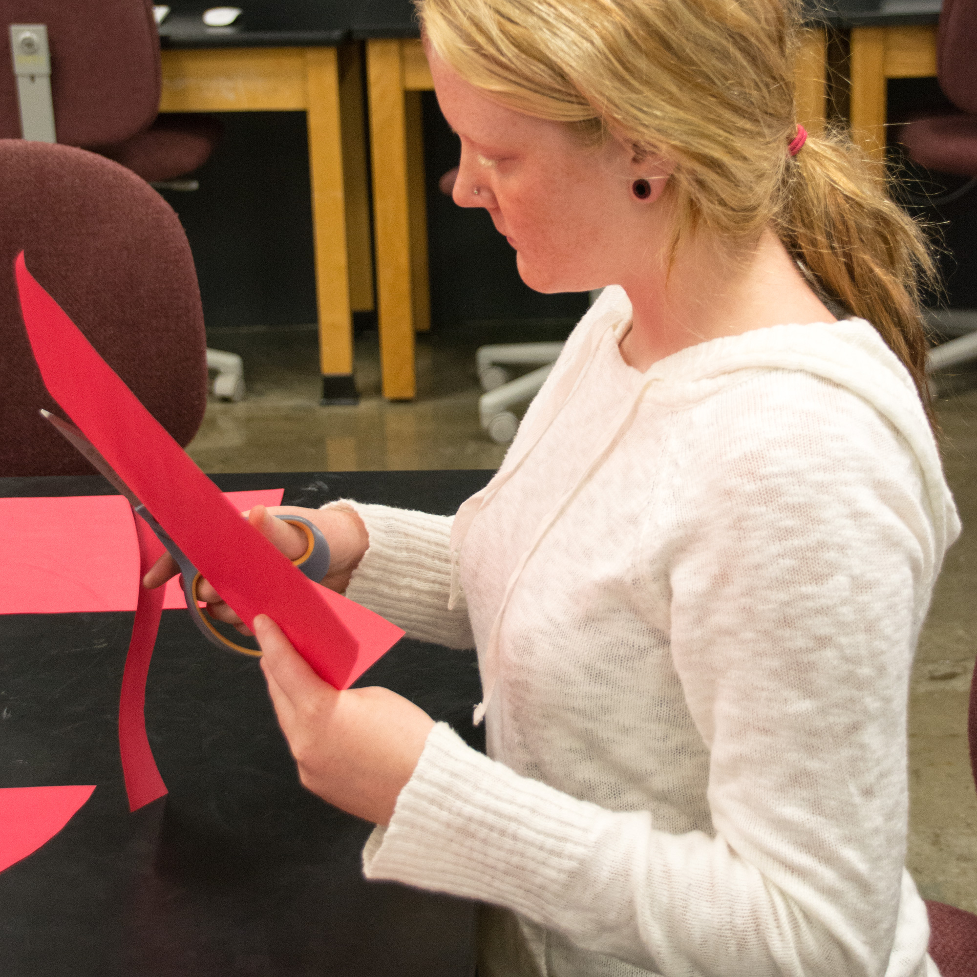 Student cutting red paper