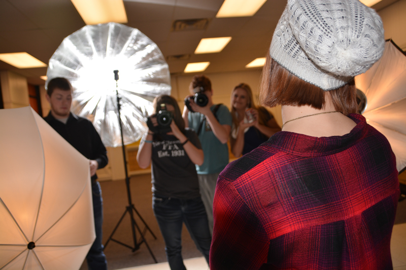 photograph from behind model focusing on two students taking a photo thereof.