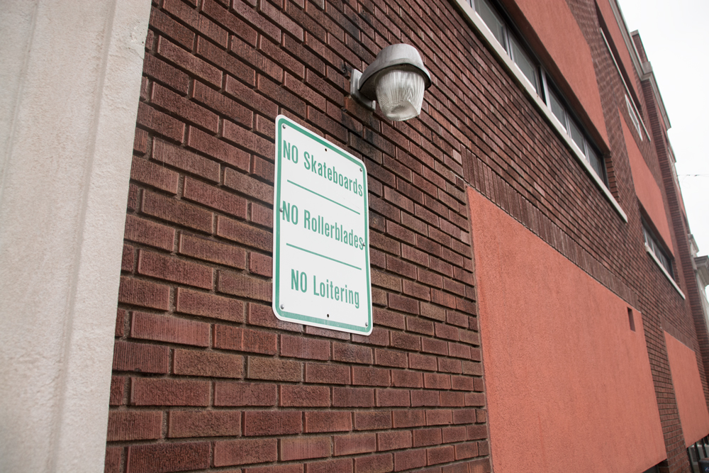 photograph of brick wall, industrial light, and no skateboarding sign.