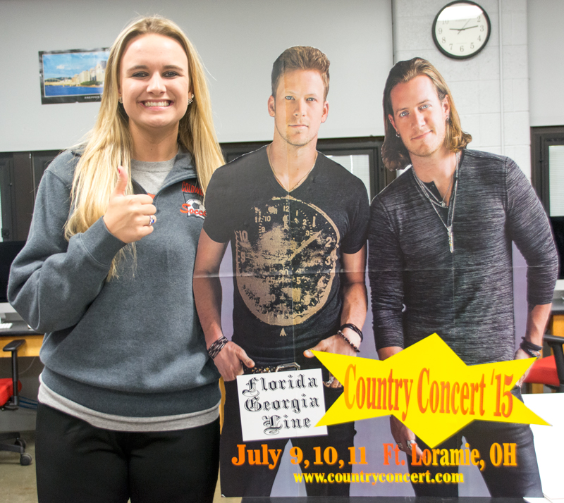 student posing with life-size cardboard cutout