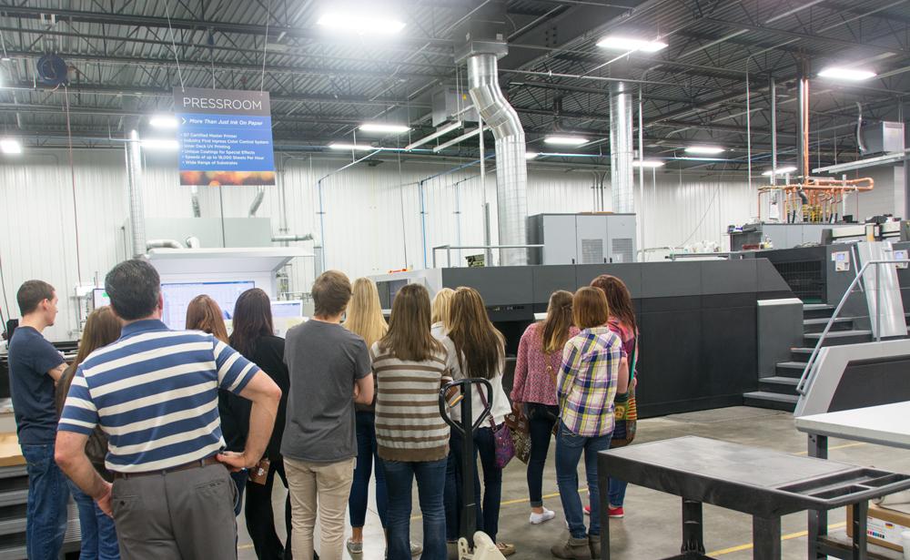 students looking at printing press