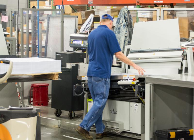 operator cutting paper on a paper cutter